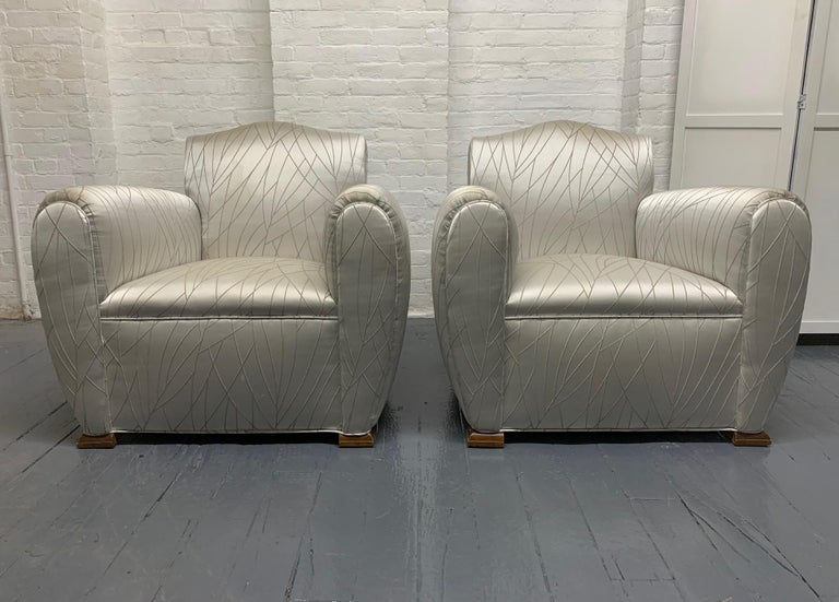 Pair of 1940s Art Deco club chairs. The chairs have walnut bracket feet and are oversized.