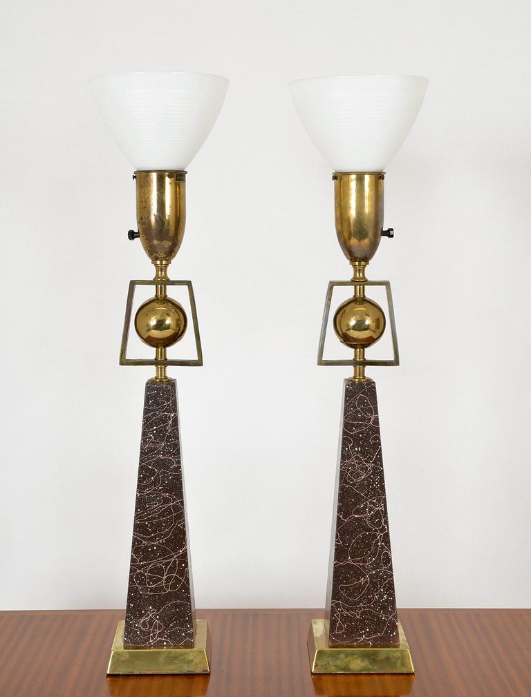 A pair of 1950s American Mid-Century Modern obelisk table lamps by Rembrandt Lighting, part of their 'Masterpieces' range. The lamps are in the form of an obelisk topped with a brass ball within a solid brass isosceles trapezoid frame, and
