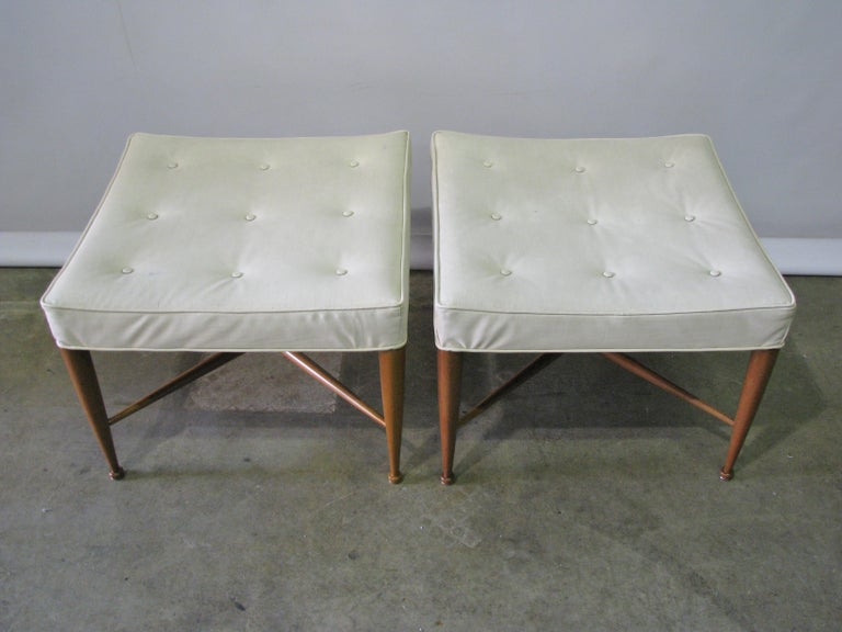 A pair of square upholstered benches each with a buttoned seat supported by walnut legs with button feet and X-stretchers. Model no. 5002. By Edward Wormley for Dunbar, American, circa 1950s. The pair has their original vinyl fabric (yes, vinyl!),