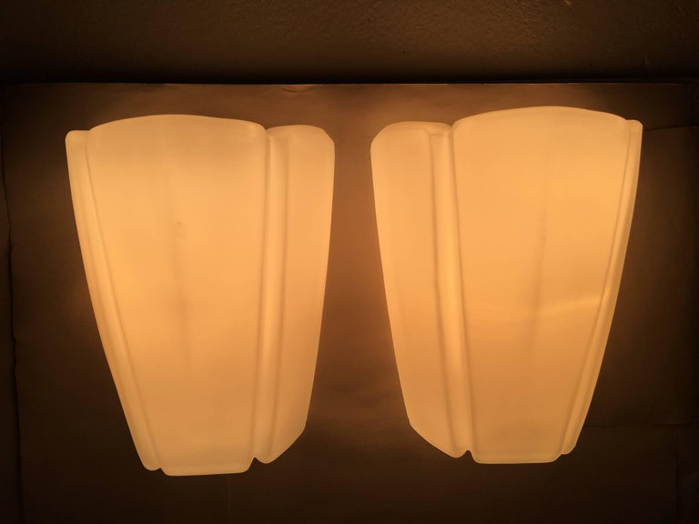 Pair of sconces by Glashutte Limburg Germany, in the rare milk glass version. In good, working condition with on / off switch in the lamp, it works by pulling on the cord. Rewired to meet U.S. standards. Each fixture requires one European E27 Edison