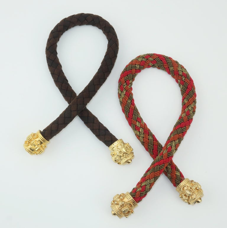 Put a little polish on your pony with these ornate hair ties.  Both pieces are braided with one in a brown ultra suede and the other in a olive green, red, rust and metallic gold silk cord.  Each end is accented with a weighty gold tip with a