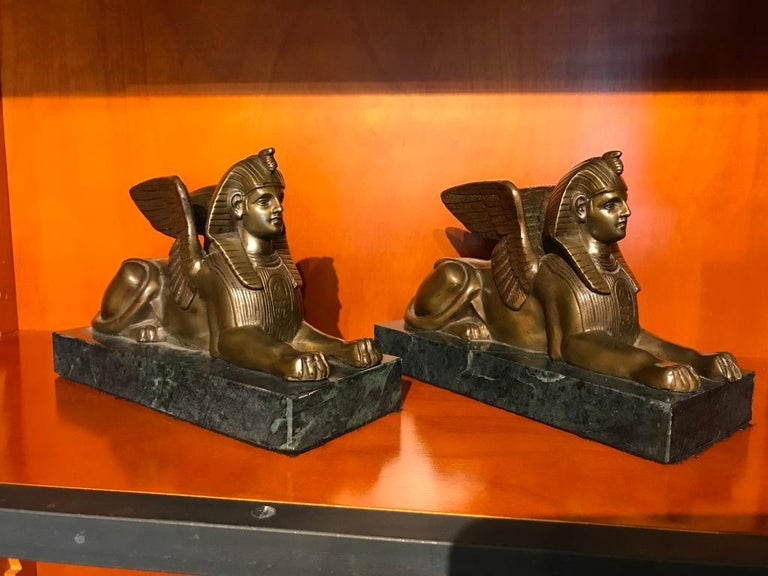 Pair French grand tour bronze sphinxes with wings mounted on green marble rectangular bases. Finished with a warm golden hued patina. Will make a fine pair of bookends or stand alone decoration. Greta for a mantle piece, den, library or bookshelf.