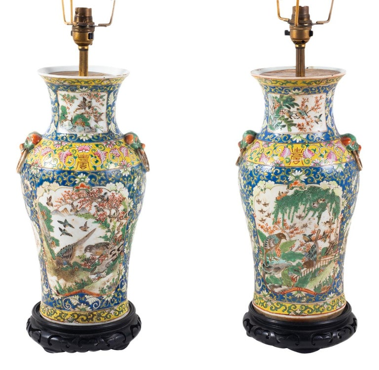 A very good quality pair of 19th Century Chinese Cantonese vases, having a blue and yellow ground with classical motif and scrolling foliate decoration around inset hand painted panels depicting exotic birds and trees, each with dog of foe mask and