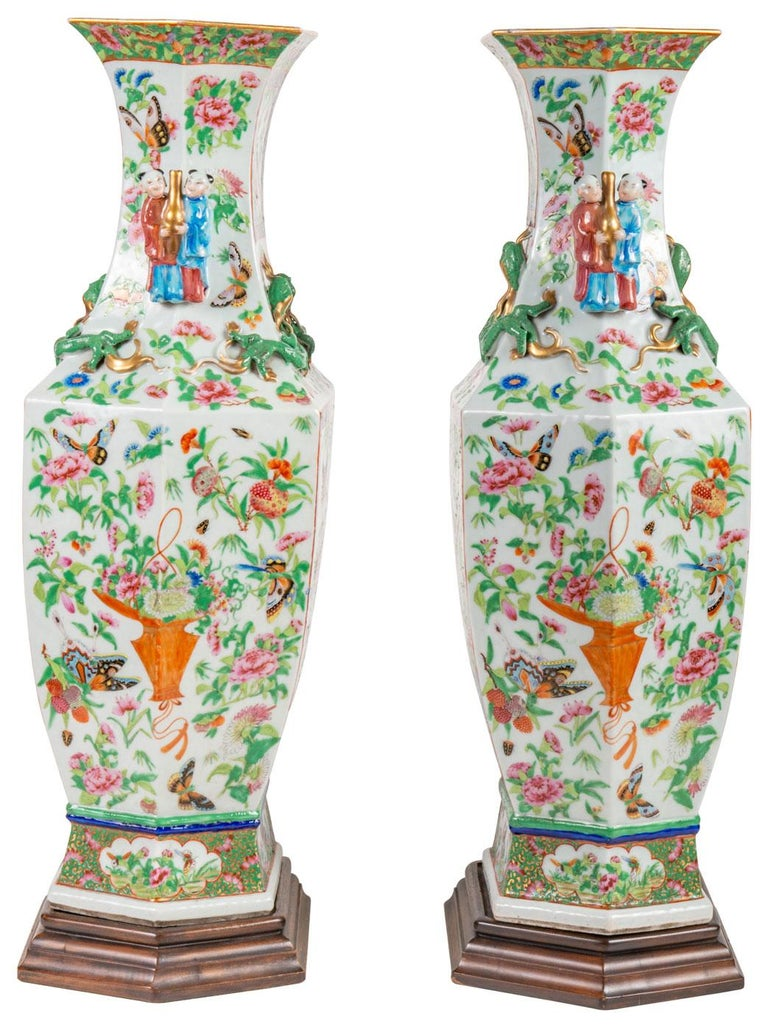 A very good quality pair of mid-19th century Chinese Canton / Rose medallion vases on stands. Each with a white ground, green foliate decoration with exotic bids, flowers and butterflies. Inset panted panels, handles either side of two men carrying