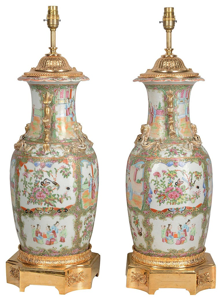 A good quality pair of 19th century Chinese rose medallion porcelain vases / lamps, each with green ground with in set hand painted panels depicting classical scenes of Geisha girls and courtiers walking around the grounds of a temple. Gilded