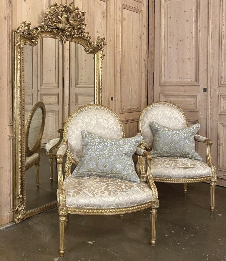 Pair of 19th century French Louis XVI Gilded armchairs ~ fauteuils are a rare find because of their size! Typical chairs from the era are smaller, so these were obviously custom ordered for what is now a more 21st century physique. Intricately