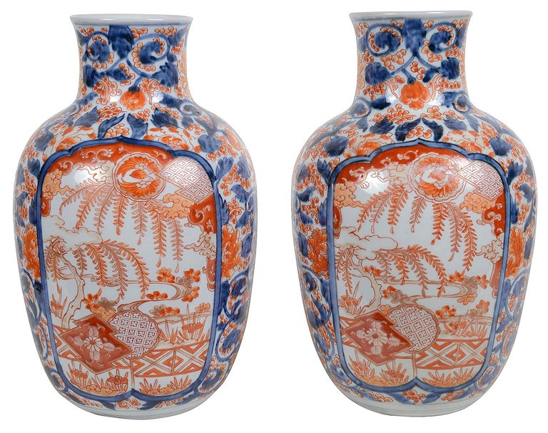 A very good quality pair of Japanese Meiji period (1868-1912) Imari vases, each with an orange and blue ground of leaves and berries, inset painted panels of exotic gardens.  The vases can be wired as lamps if required within the price.