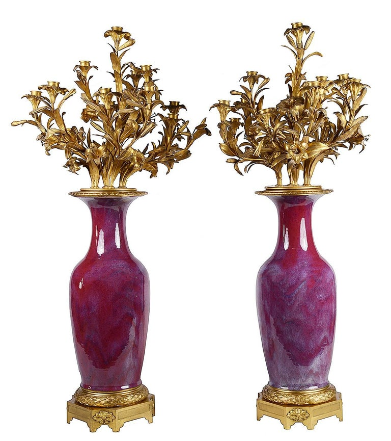 A very impressive and imposing pair of 19th century Chinese Sang De Boeuf vases with gilded French ormolu 14 branch floral and leaf candelabra, and mounted on leaf and floral bases.