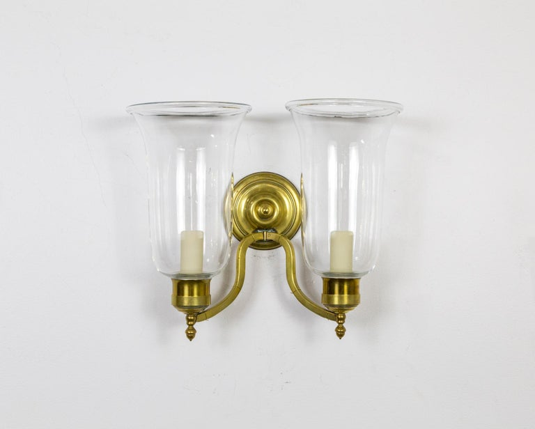 A fine pair of neoclassical style, extended double arm, brass sconces with heavy, blown glass chimney shades and rosette detail. American, 1980s. Recently restored and rewired.