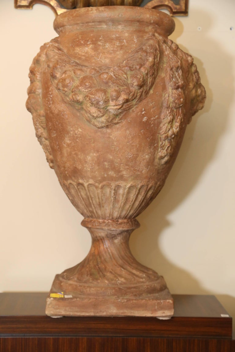 Pair of terra cotta urns with Della Robbia garland motif,  20th century, Italian.