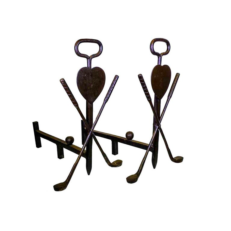 Pair of 20th century, Folk Art, golf themed andirons, having a central shaft with a loop handle and a pair of golf clubs centering a heart, the forward log stop is in the form of a golf ball. Made of wrought iron they appear to be blacksmith made.