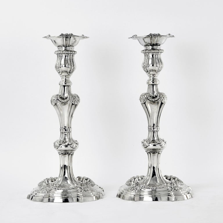 A spectacular pair of George III cast silver candlesticks made by Frederick Vonham in 1762 with the addition of a pair of 3-light arms by the same maker in 1771. The shaped, round bases have a border of four shell motifs connected by a heavy gadroon