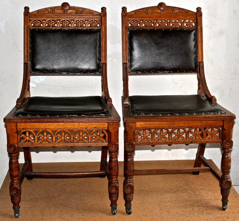 Aesthetic movement chairs beautifully carved oak or ash with great detail. Leather upholstered. India rubber Company New York wheels.