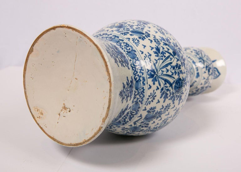 We are pleased to offer this exquisite pair of Dutch Delft blue and white vases. They are hand-painted in a medium cobalt blue with an all around scene in the