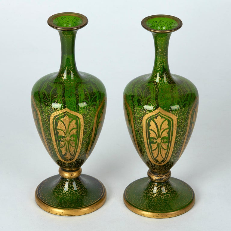 A very fine antique pair Bohemian green glass vases decorating with gilding, possibly Moser dating from the latter 19th century. The beautifully made vases stand on a rounded pedestal base with knop stem supporting a pear shaped body with tall