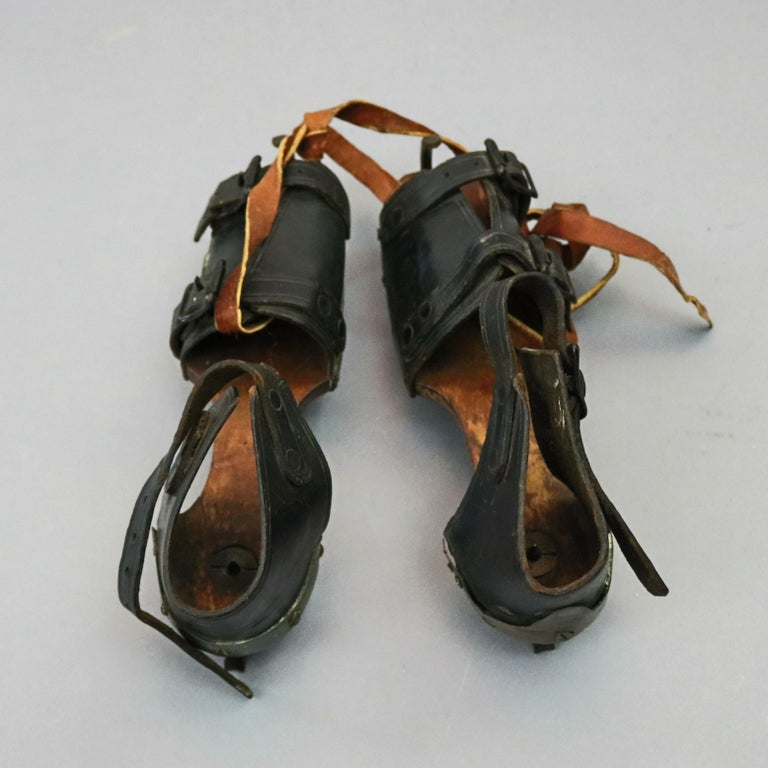 A pair of antique ice skates feature leather shoe with buckles mounted on carved wood bases with skating blades, 19th century  ***DELIVERY NOTICE – Due to COVID-19 we are employing NO-CONTACT PRACTICES in the transfer of purchased items.
