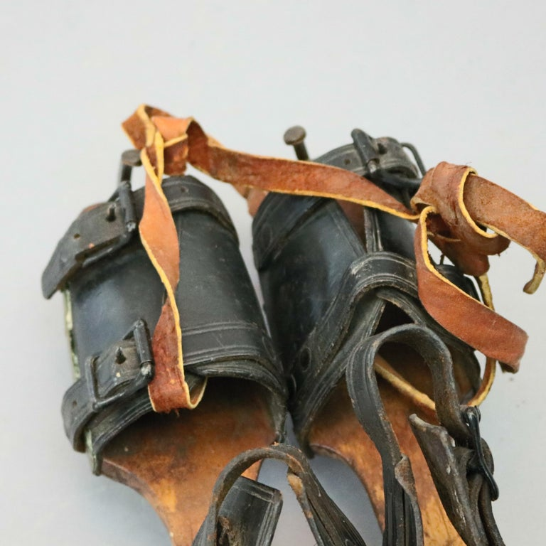 Carved Pair of Antique Buckled Leather and Wood Ice Skates, 19th Century For Sale