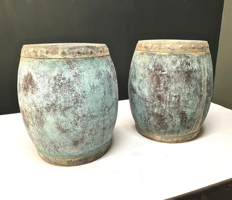 This is a unique pair of antique copper rice storage barrels in the form of garden seats. Both barrels are in very good structural condition and have acquired a deep rich verdigris patina. Beneath the patina are engraved/etched designs; there is a