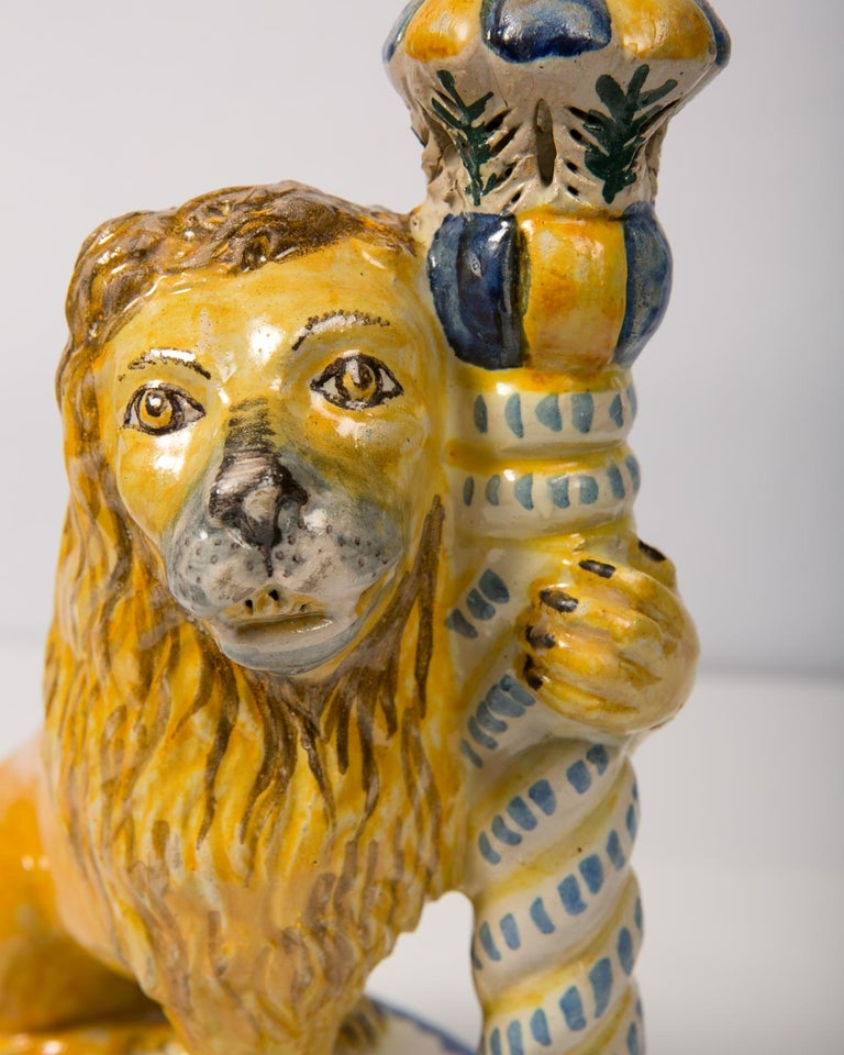 A superb pair of antique faience lions holding candlesticks. These lions have lots of personality with friendly smiling faces. Made in Italy in the mid-19th century. They have coats with a warm golden color which enhances the blue and gold of the