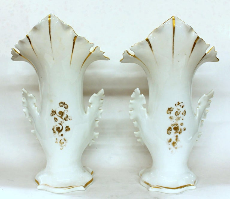 Pair of exquisite quality antique French hand painted porcelain flair vases with exceptionally hand painted botanical sprays to the front and gilt decorative motif to the rear. There are no damages whatsoever and only the slightest bit of gilt