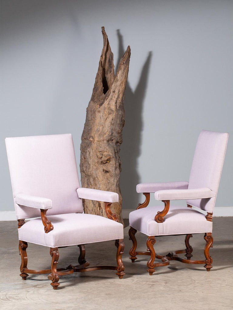 This pair of grand scale antique French Louis XIV Régence style walnut armchairs circa 1875 possess a handsome monumental appearance. Please enlarge the photographs to see the unique details in closeup including the luscious patina of the walnut