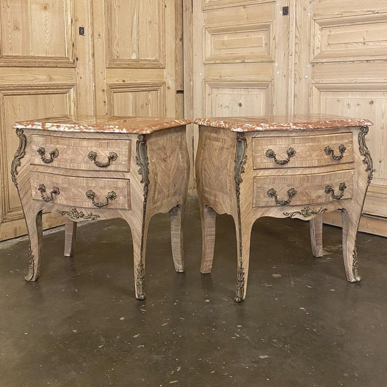 Pair of antique French Louis XV marble-top marquetry commodes are a delightful expression of the genre, with exotic mahogany and fine walnut veneering arranged in an artistic pattern atop the bulbous contours of the sides and front. Two spacious
