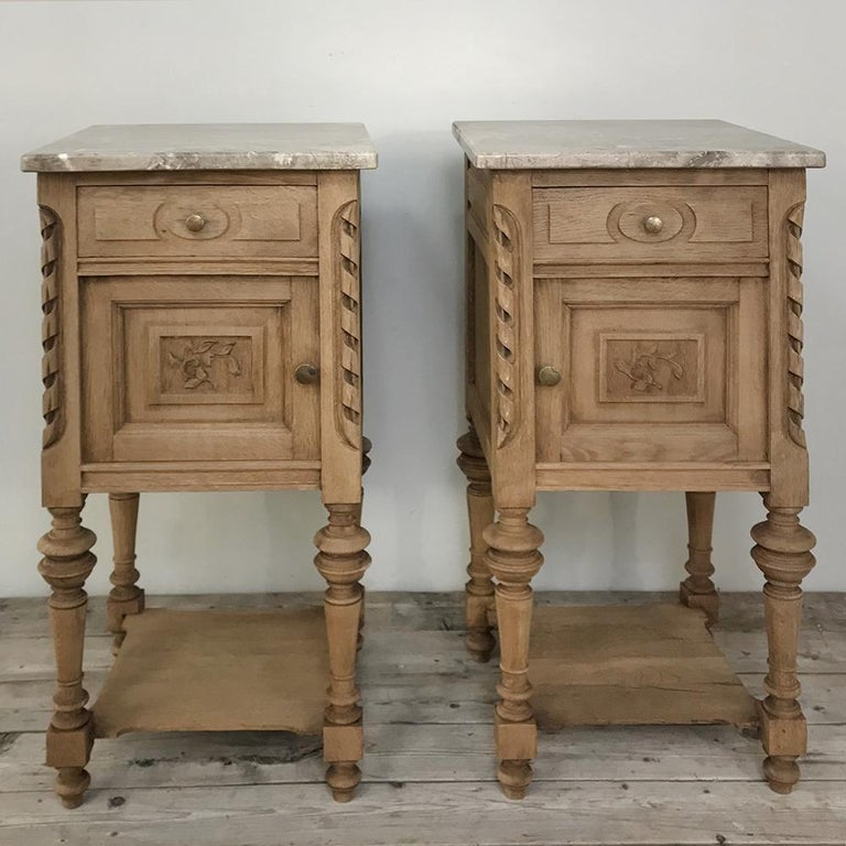 Pair of antique French Louis XVI stripped marble top nightstands feature tailored neoclassical lines, cabinet and drawer each and luxurious carefree marble tops with a splendid neutral color and subtle veining. Lower shelf adds a convenient surface,