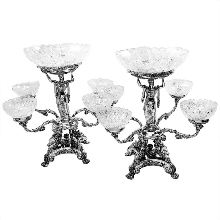 A pair of magnificent antique George IV Epergnes with elegant sterling silver classical figures supporting the central cut glass bowl. The rest of the impressive centrepiece is made in traditional Old Sheffield plate and four branches support four