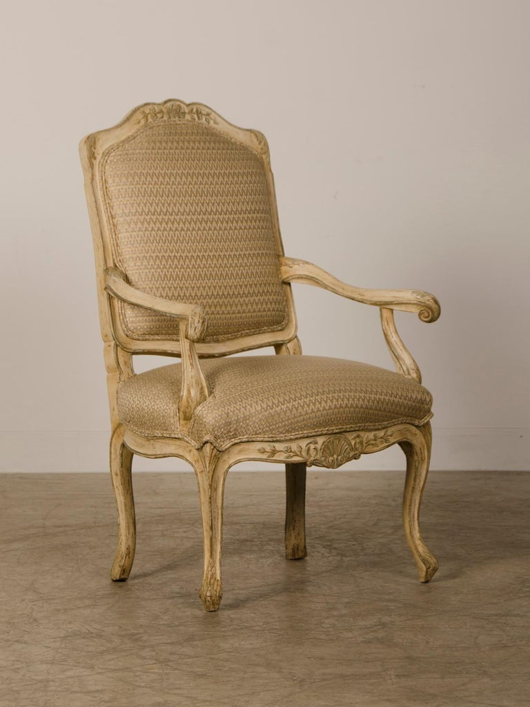 A pair of antique Italian Louis XV period painted armchairs from Italy circa 1770 having elegant carved detail each with a graceful shaped back and dramatically sloping arms with a shaped seat showcasing an apron with a cartouche in the centre and