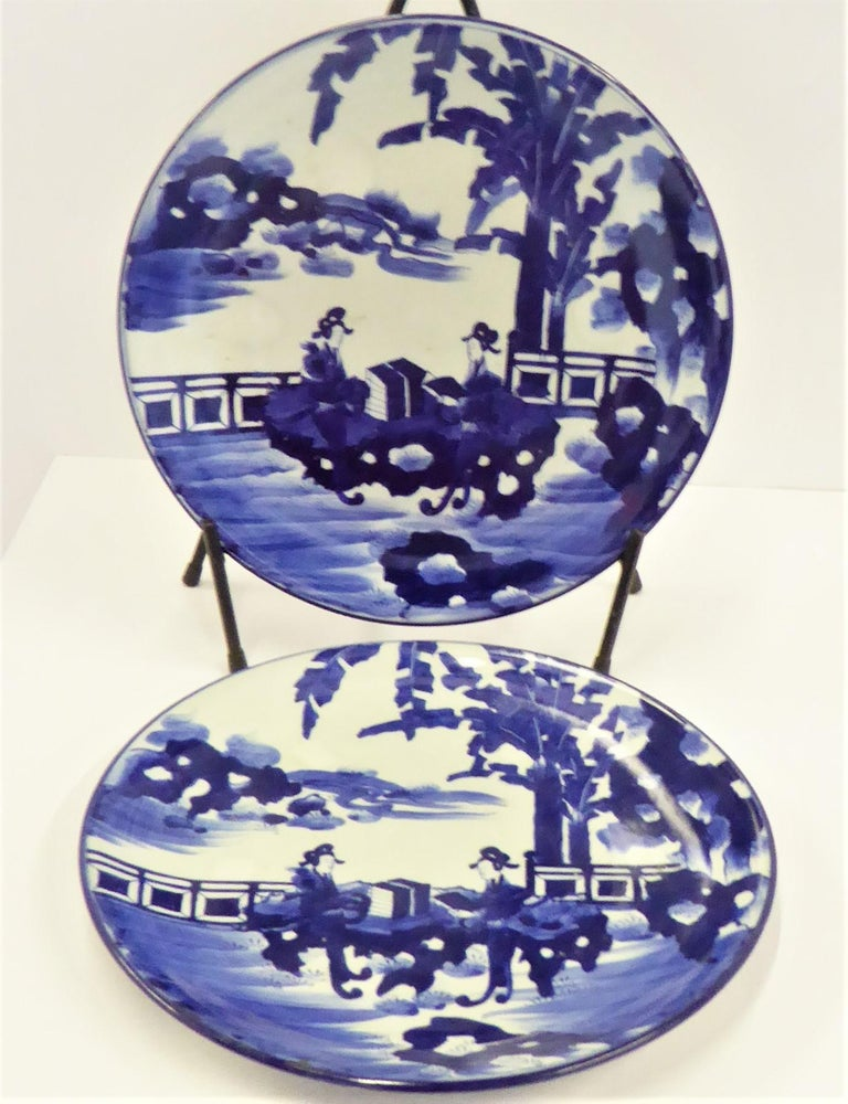 Beautiful pair of Meiji Period blue and white Japanese Imari Chargers depicting two Japanese Courtesans reading poetry by a lake in a serene setting framed by banana palms or trees on one side of background. Matching in design, both platters have
