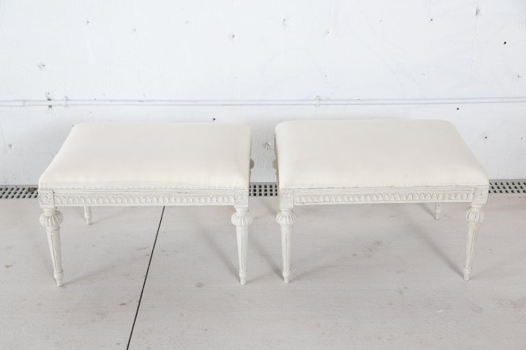 Pair of antique Swedish Gustavian style stools, with tapered fluted and carved legs. Seat apron edge is beautifully carved with egg and dart design. Wood painted in Swedish white color. Upholstered seat top