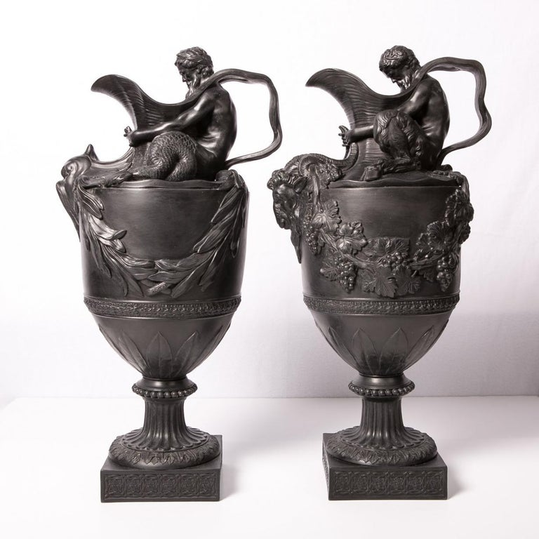 A pair of antique Wedgwood black basalt wine and water ewers named: