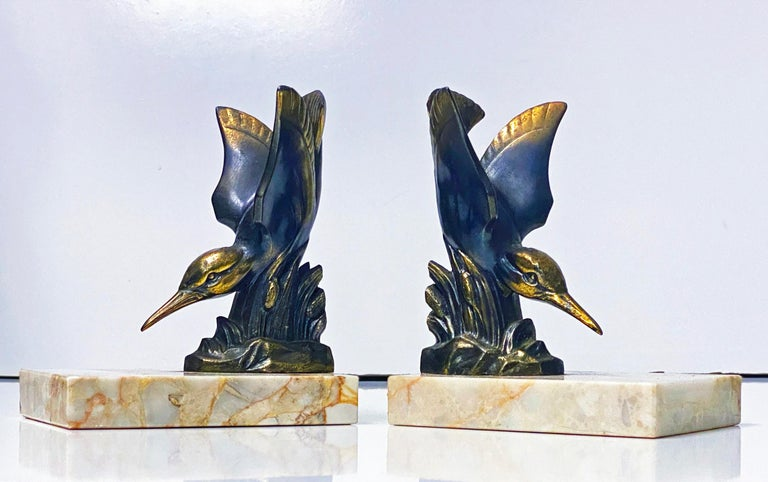 Pair of Art Deco Bronze Kingfisher bookends, France, circa 1930. Each depicting a Kingfisher on marble base. The diving kingfisher realistic model form, patinated bronze body; surmounted on mottled light brown and cream overtone base. Each overall