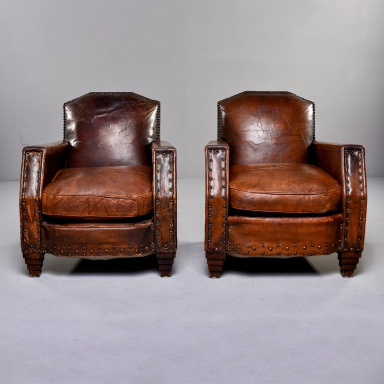 """Pair of English Art Deco era circa leather armchairs in original brown leather date from the 1930s. Trimmed in brass nailhead tacks, stepped front legs. Unknown maker. Sold and priced as a pair.  Measures: Arm height 23.25"""", seat height 19""""  Seat"""
