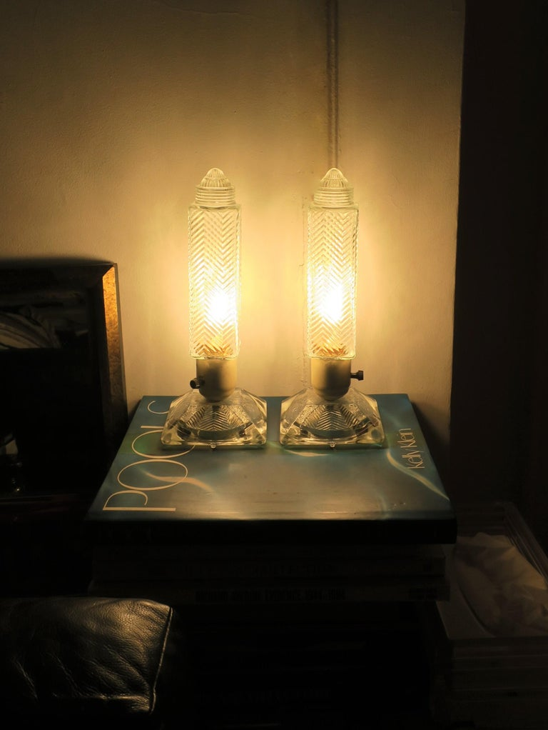 A pair of Art Deco period glass table or bedside/nightstand lamps, circa 1930s. Lamps have all the beautiful design hallmarks of the Art Deco period including the chevron pattern on glass lamp shade and base, as show in images. Lamps shown in 'on'