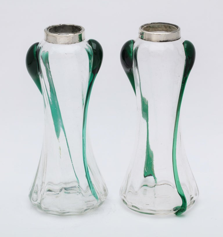 Pair of unusual, Art Nouveau, sterling silver-mounted hand blown dark green and clear glass bud vases, London, 1904, A. Bromet and Co. - makers. Each vase stands 6 1/2 inches high x 2 3/4 inches diameter (at widest point) x 1 1/2 inches diameter