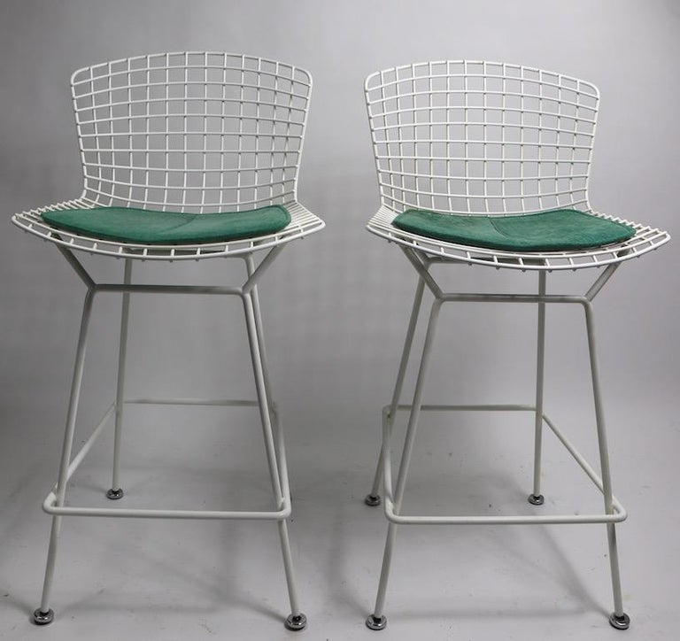 Classic and iconic Bertoia for Knoll bar or counter height stools in white with green fabric pads. Architectural design, clean original condition, ready to use. Both pads retain original Knoll label. Offered and priced individually, however we would