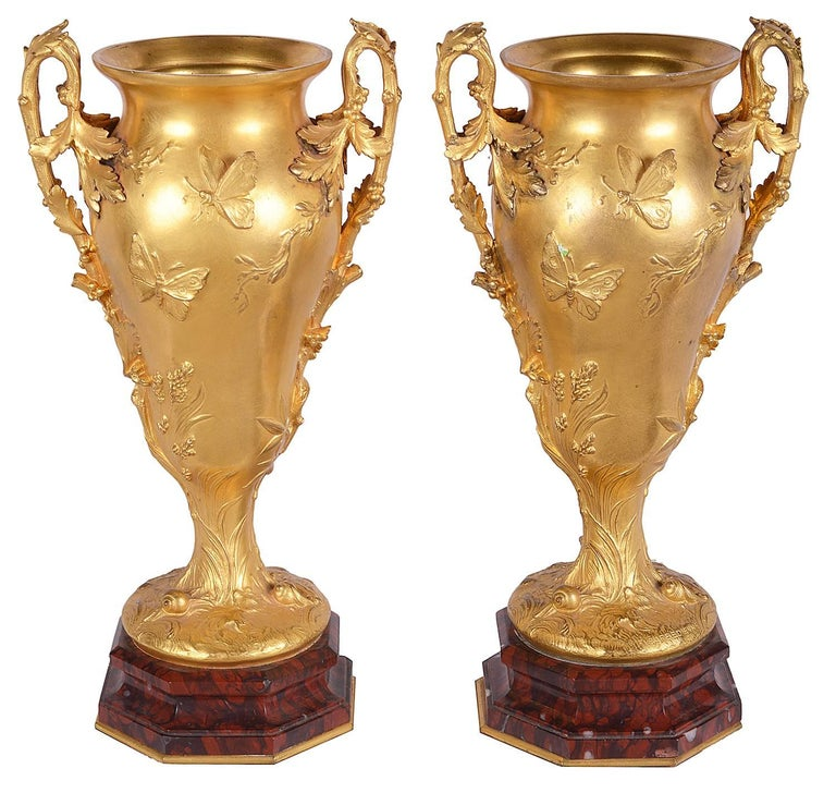 A very good quality pair of twinned handled gilded ormolu and rouge marble urns. Each having raised foliate decoration with exotic birds and butterflies, mounted on rouge marble bases. Signed; Barbedienne.