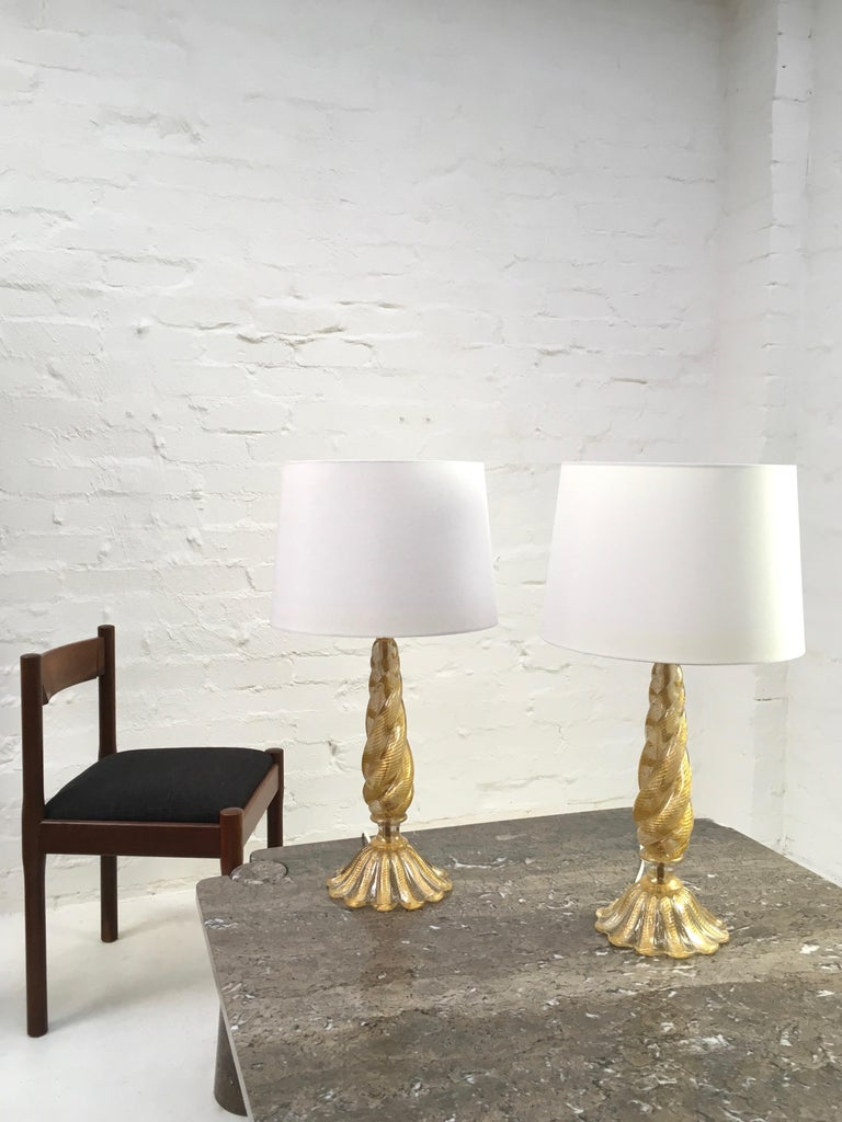 A pair of table lamps by Barovier and Toso, dating to the 1950s, with gold leaf inclusions in the 'Cordonato d'Oro' technique. They appear as twisted ropes of gold in each section of glass. 
