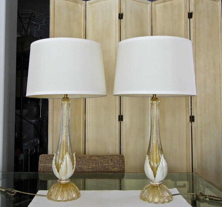Pair of hand blown Murano glass table lamps, with clear and gold inclusions using 'Cordonato d'Oro' technique. The glass is expertly hand blown with fine detailing throughout, including ribbed body and cream applied acanthus leave accents. Newly