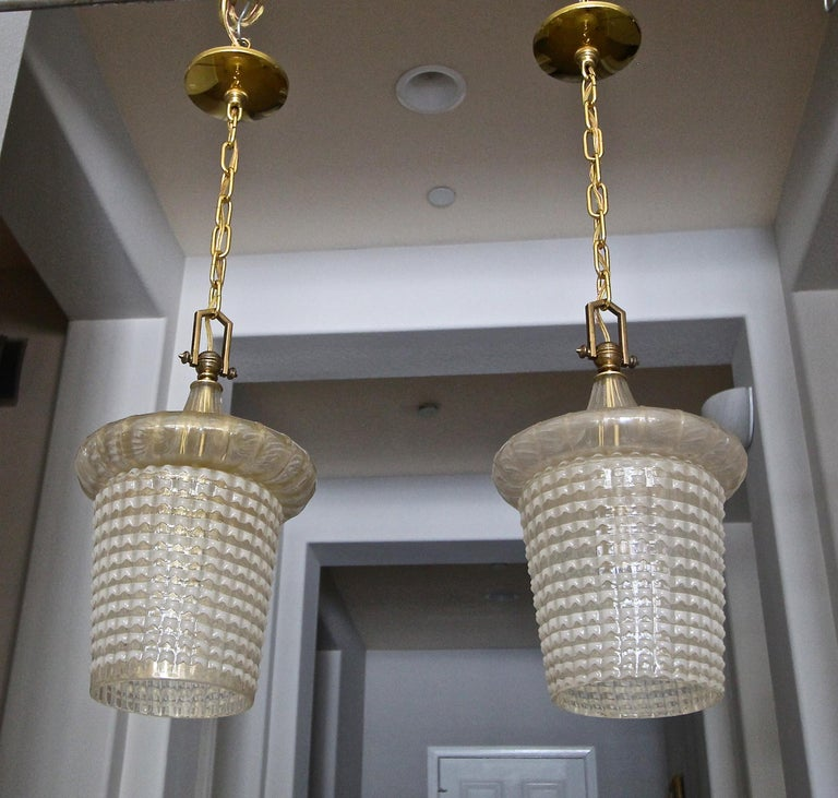 Pair of lantern shaped Murano ceiling light pendants by Ercole Barovier Toso. The top portion is ribbed with gold inclusions, the bottom half is in the
