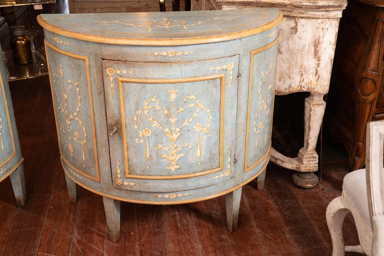 Beautifully painted pair of demilune buffets with original paint. Muted colors can fit in with any décor, circa 1890.