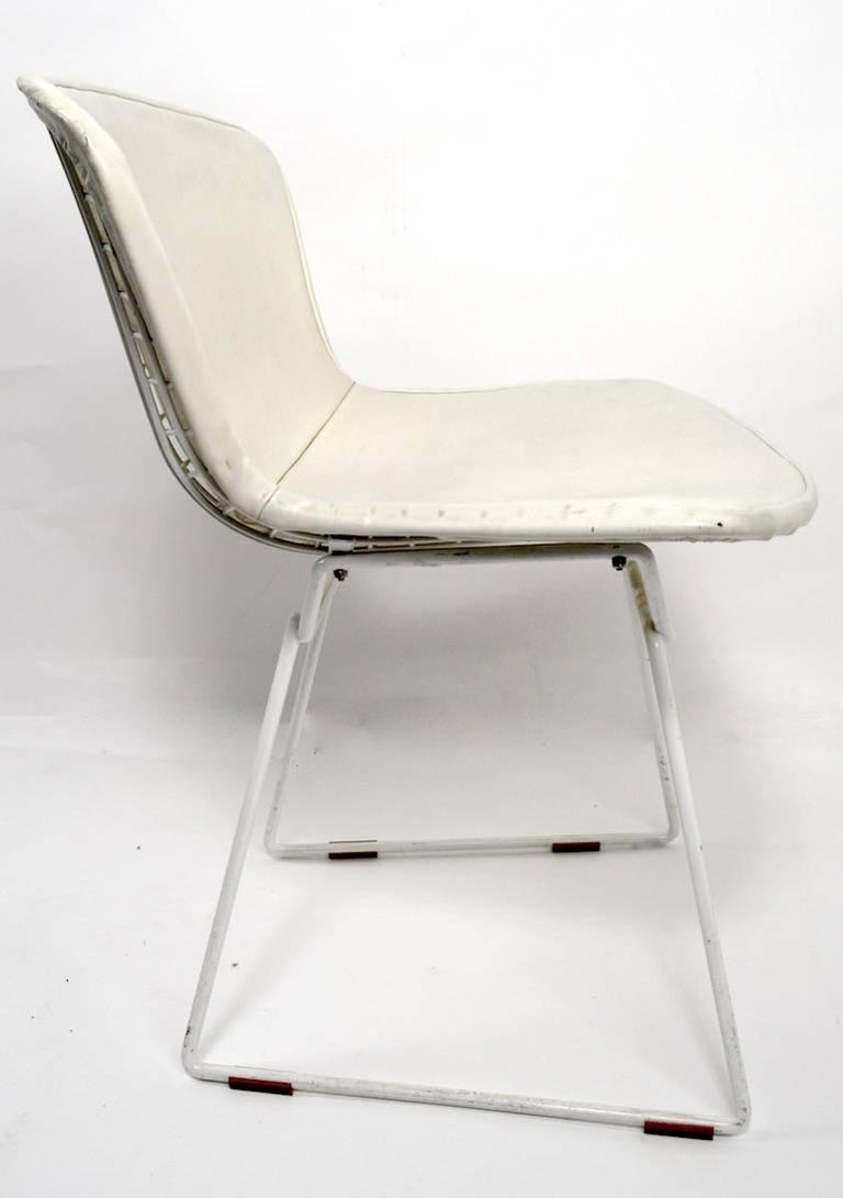 Pair of Bertoia design for Knoll wire dining chairs, with off-white pad seats. Nice vintage pair retaining the original Knoll label (655 Madison Ave). Measures: Seat height 18, fine, original condition, showing only light cosmetic wear, normal and