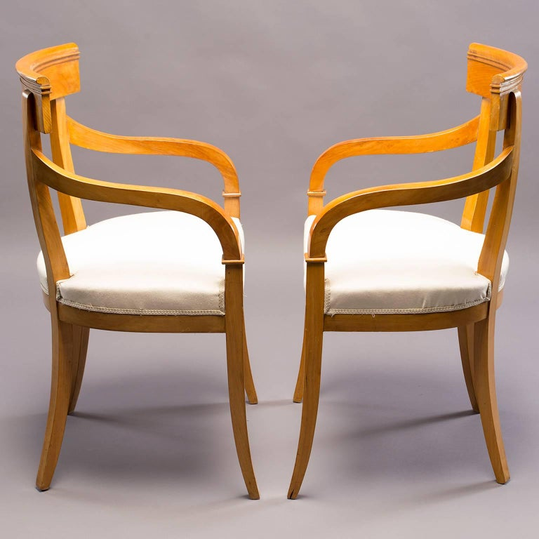 """Pair of Biedermeier style armchairs with clean, simple lines in lighter wood believed to be birch, circa 1930s. Seats have muslin cover and are ready to be upholstered in fabric of your choice. Graceful curved arms are 25.75"""" high and seats are"""