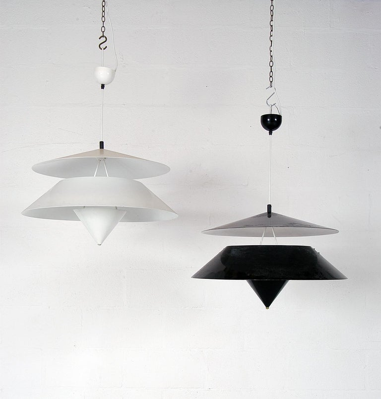 Rare harlequin pair of 1970s 'Kalaari' ceiling pendants designed by Vico Magistretti for Oluce, Milano. One in black paint, one in white - these large 65cm diameter lights make a huge statement! With the bulb nestled in the inverted cone at the