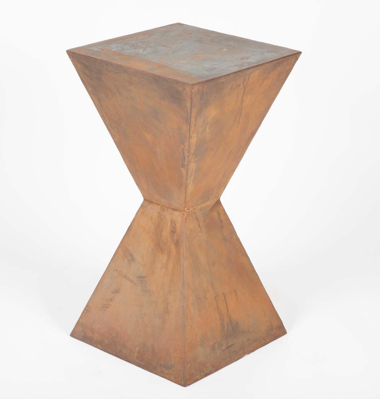 Compelling pair of geometric steel side tables in very much in the style of Constantin Brancusi. With a soft rust colored patina, these can also be used a wonderful pedestals for sculpture or other objects.