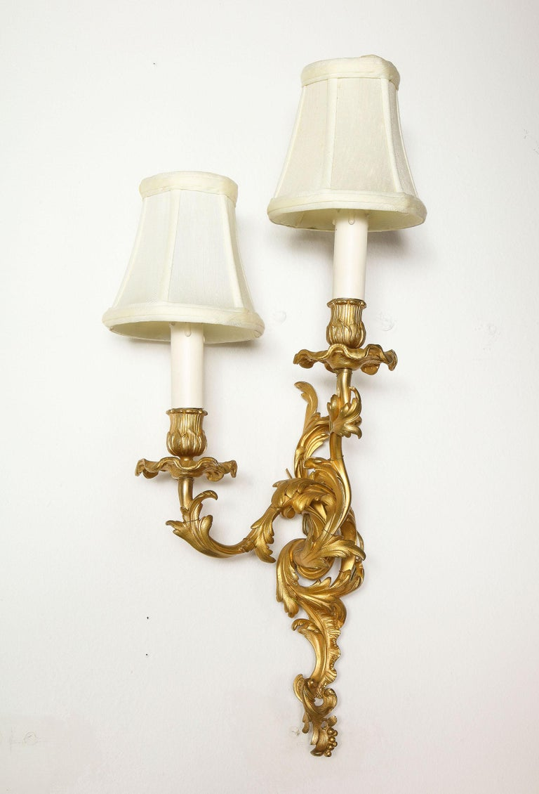Probably Napoleon III in the Louis XV style, the chased bronze wall lights each with a scroll work back plate supporting a staggered pair of similarly scrolled arms.