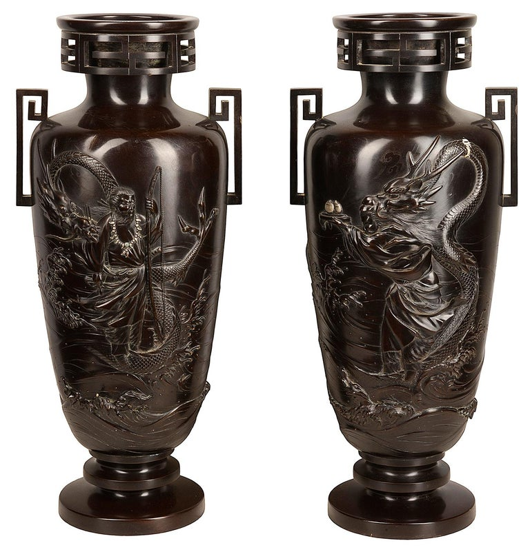A pair of Japanese cast bronze vases, each of slender tapered form resting on a stepped base and rising to a narrow neck with everted, key-fret rim, applied to the shoulder with rinzu handles, each decorated with a mythical figure, one offering a