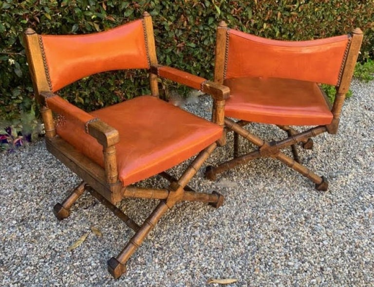 A wonderful pair of wood and orange leather campaign style chairs. The fabric is original and does have some wear, but overall is wonderfully patinated with a worn in look. The wood frames are very sturdy and perfectly suited for any den or living