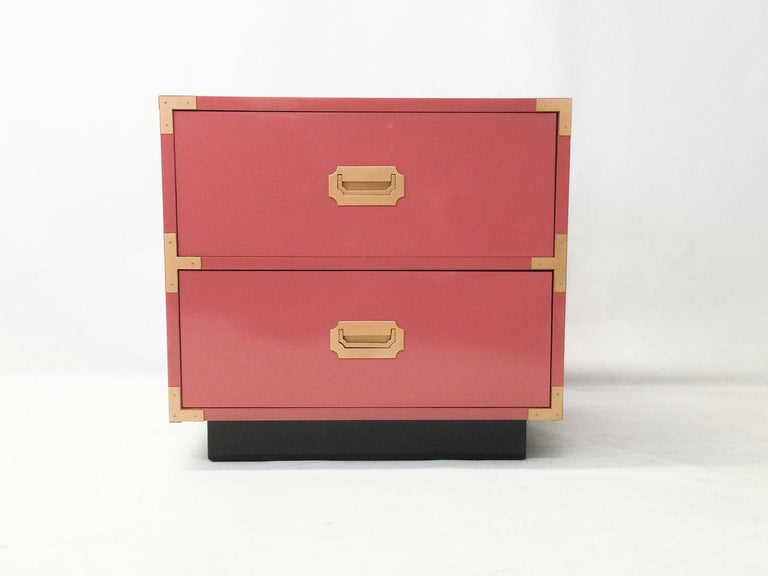 Pair of Campaign style nightstands are always pretty in pink! These have been professionally lacquered in pink with a black base. Solid wood construction these feature plenty of storage, two drawers with recessed polished brass pulls resting on a